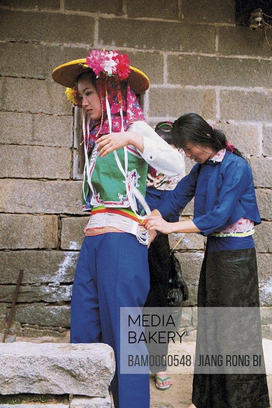 Huian Lady Tying A Girdle to young woman's waist, Chongwu Town, Huian County, Fujian Province, People's Republic of China