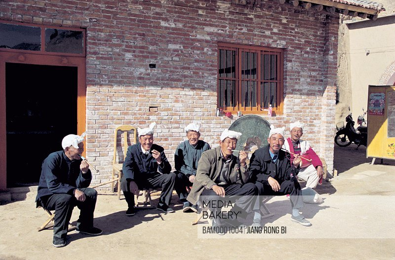 North Shanxi men in front of bricked house and holding pipe, Yichuan County, Yan'an City, Shanxi Province, People's Republic of China