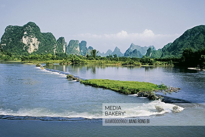 View of a river with mountains in the background, The scenery of Yulong river, Yangshuo, Yangshuo County, Guilin City, Guangxi Zhuang Nationality Autonomous Region of People's Republic of China