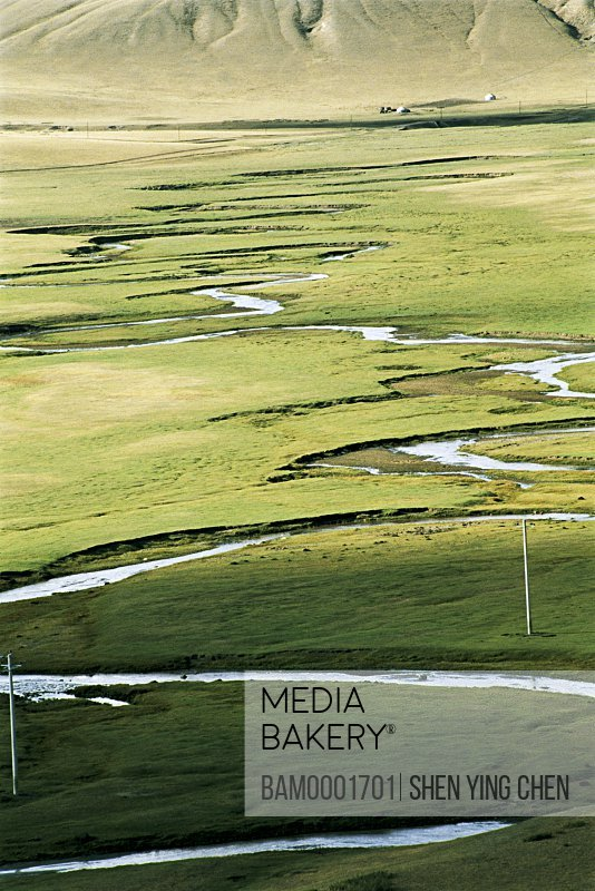 Elevated view of meandering stream passing through grassland, Scenery of the Bayangaole Prairie, Keshiketengqi, Chifeng City, Inner Mongolia Autonomous Region of People's Republic of China