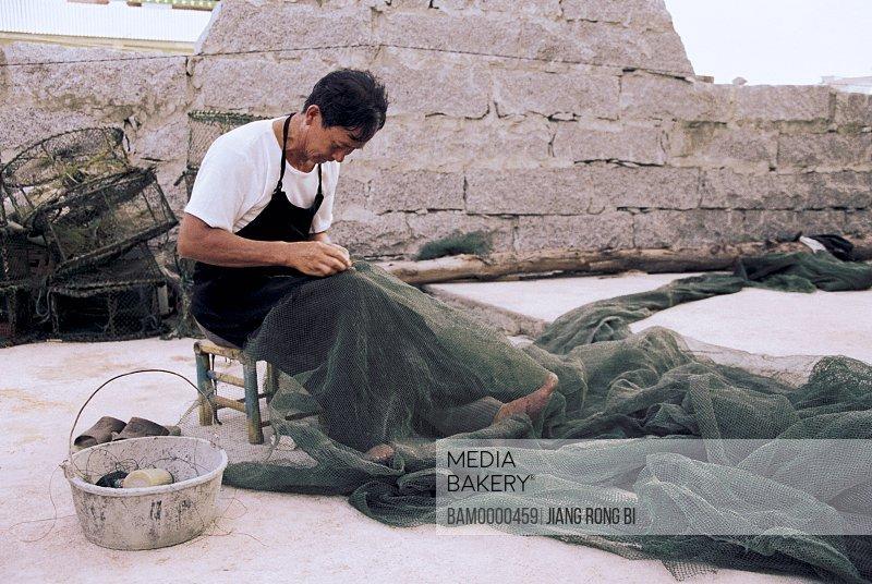 Person mending a fishing net, Pingtan County, Fujian Province, People's Republic of China