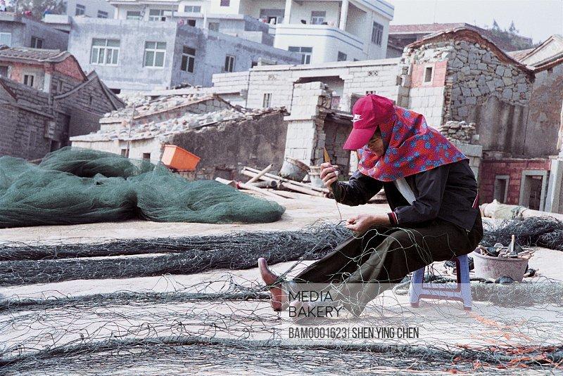 The Huian Women exposes the sun-dried shelled shrimp in the sunshine at the Xiaozuo Village seashore, Xiaozuo wharf, Huian County, Fujian Province of People's Republic of China