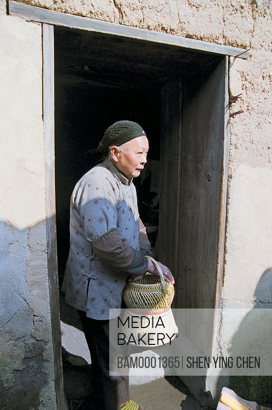 View of senior woman holding a handbasket, Ancient common people residence of Ming and Qing Dynasty at old Heping town in Shaowu, Heping town, Shaowu County, Fujian Province of People's Republic of China