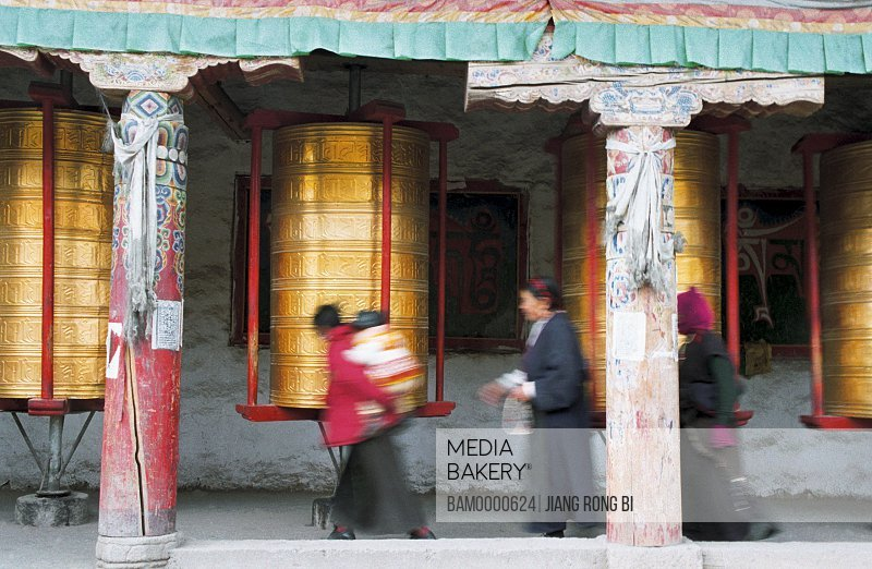 People walking by prayer wheels in shrine, The buddhist white tower and typecasting sutra wheel, Kangding County, Ganzi State, Sichuan Province of People's Republic of China