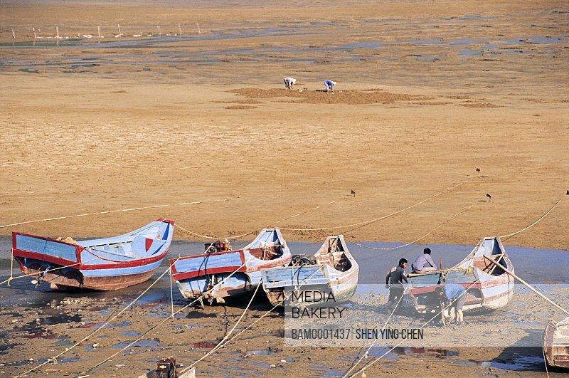 View of men standing by boat, The fishing boat at seashore of the Xiaohao , Xiaohao, Xiaopu County, Fujian Province of the People's Republic of China