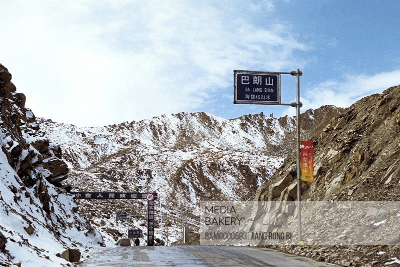 View of signboard by a road with mountains in background, The scenery of Balang Mountain , Xiaojin County, Aba State, Sichuan Province of People's Republic of China