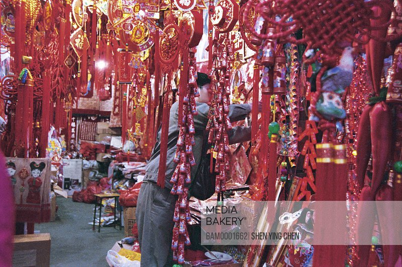 Man standing in store with decorative spring lanterns, Early spring lanterns market of south back street, Back South street, Fuzhou City, Fujian Province of People's Republic of China