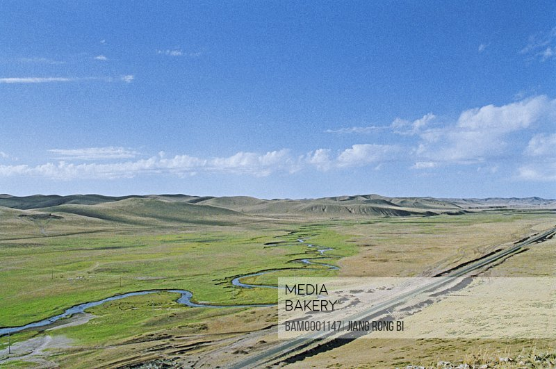 Elevated view of meandering stream passing through grassland, The landscape of the grassland in Gonggeer, Keshiketengqi, Chifeng City Inner Mongolia Autonomous Region of People's Republic of China