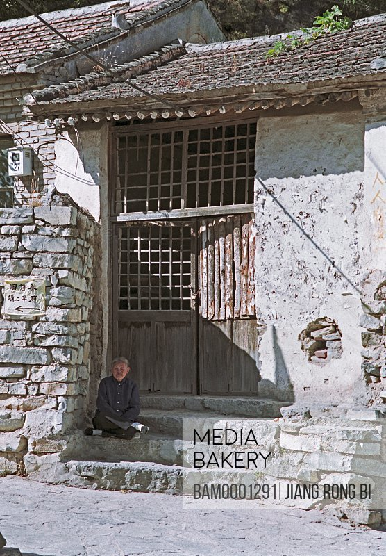 Man sitting on step by stone wall, The oldster of the Chuandixia ancient village, Beijing City of People's Republic of China