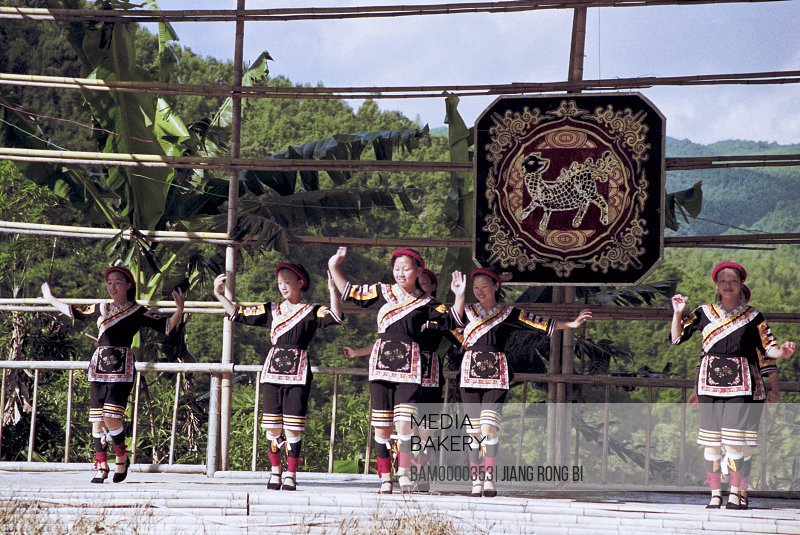 Teenage girls dancing on a bamboo structure, She minority village in Rixi township, Fuzhou City, Fujian Province, People's Republic of China