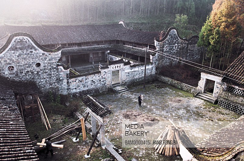 Elevated view of man holding child in courtyard, Large Courtyard of Ancient House, Taishun County, Zhejiang Province, People's Republic of China