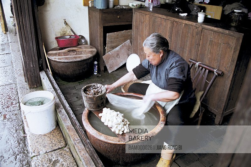 Senior woman dyeing silk cloth, Old woman handwork suppresses the silk in Wu town, Wu Town, Tongxiang City, Zhejiang Province, People's Republic of China