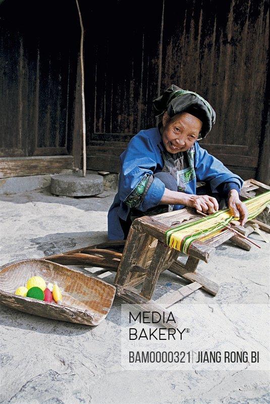 Portrait of a cheerful Miao minority older woman making a brocade in Miao minority housing of Dehang, Jishou City, Xiangxi Prefecture, Hunan Province, People's Republic of China