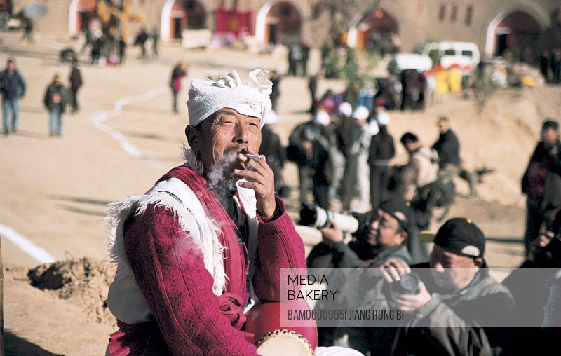 Old Man of North Shanxi smoking with tourists standing in the background, Yichuan County, Yan'an City, Shanxi Province, People's Republic of China