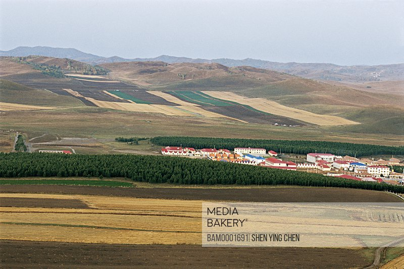 View of houses amid landscape with mountains in background, The Lama mountain scenery of the Sehanba Prairie, Saihanba Prairie, Fengning County, Hebei Province of People's Republic of China