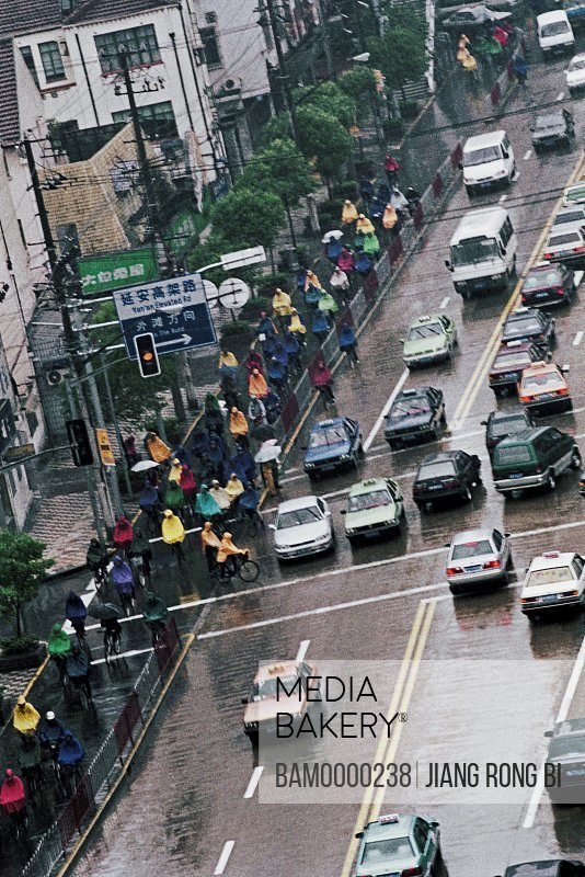 Cars and people moving on rainy street, The rainy street of Jingsu Road, Shanghai City of People's Republic of China