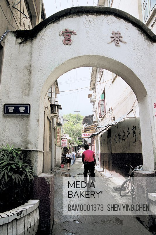 Rear view of a man riding bicycle on a lane, Three work place seven lanes---Palace lane, Gongxiang entrance, South street, Fuzhou City, Fujian Province of People's Republic of China