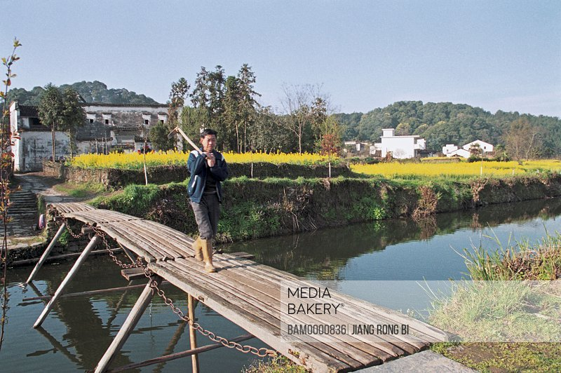 Man walking on bridge over water with houses in the background, The peasants of Yan Village, Yancun Village, Wuyuan County, Jiangxi Province of People's Republic of China