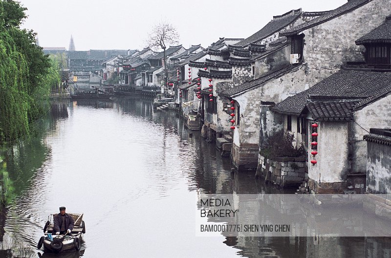 Man with boat in lake by houses, The old town scenery of West region of rivers and lakes pond , Jiaxing City, Zhejiang Province of People's Republic of China
