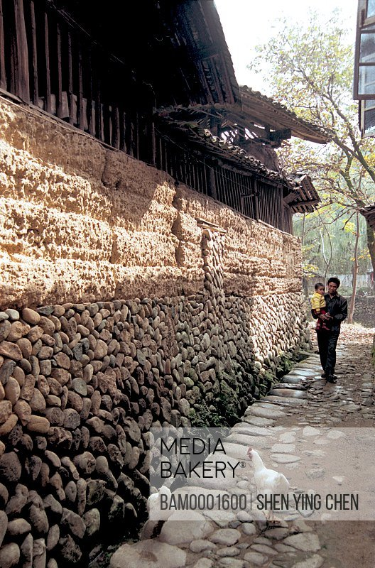 Father carrying son in alley beside stone wall, The Villagers and Village of the Shouning County, Shouning County, Fujian Province of People's Republic of China