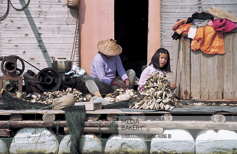 Woman and girl with oyster sitting by door, Fisherfolk Digging for Oyster in Farm, Luoyuan County, Fuzhou City, Fujian Province, People's Republic of China