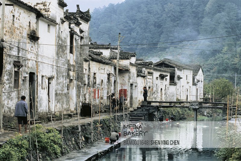People washing clothes in stream with mountains in background, Ming and Qing dynasty historic building of Likeng village, Likeng Village, Wuyuan County, Jiangxi Province of People's Republic of China