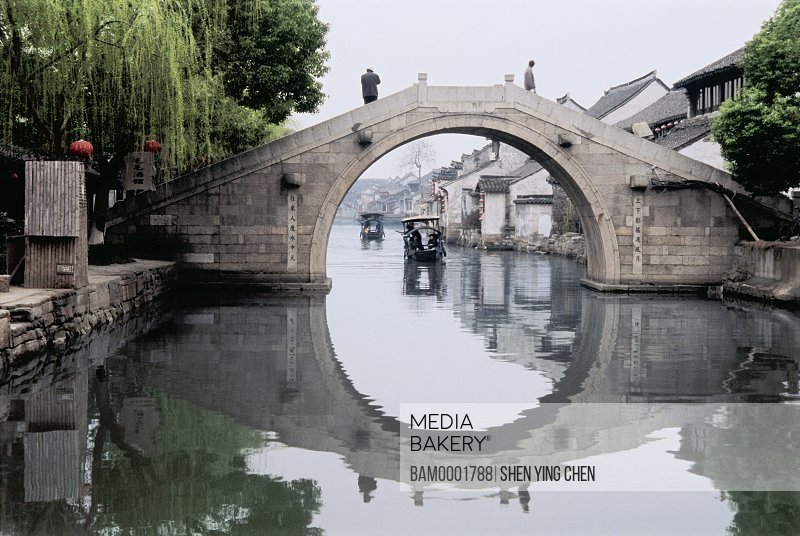 Reflection of bridge in canal with boats in background, Ming and Qing dynasty historic building of old Xitang Town, Jiaxing city of Zhejiang province in People'c republic of China