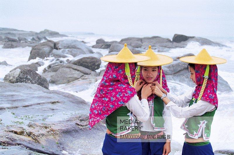 Girls standing on rocks by beach, Attractive Huian Ladies on Beach, Chongwu Town, Huian County, Fujian Province, People's Republic of China