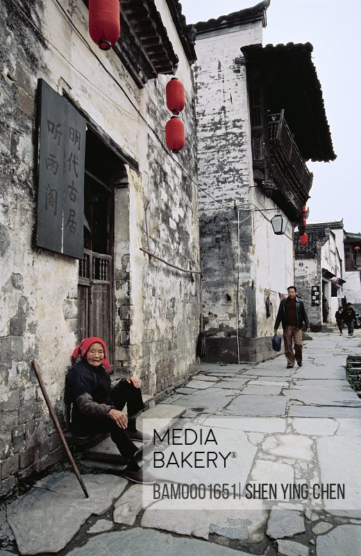 Old woman sitting on pavement by doorway, Ming and Qing dynasty historic building of Likeng village, Likeng Village, Wuyuan County, Jiangxi Province of People's Republic of China