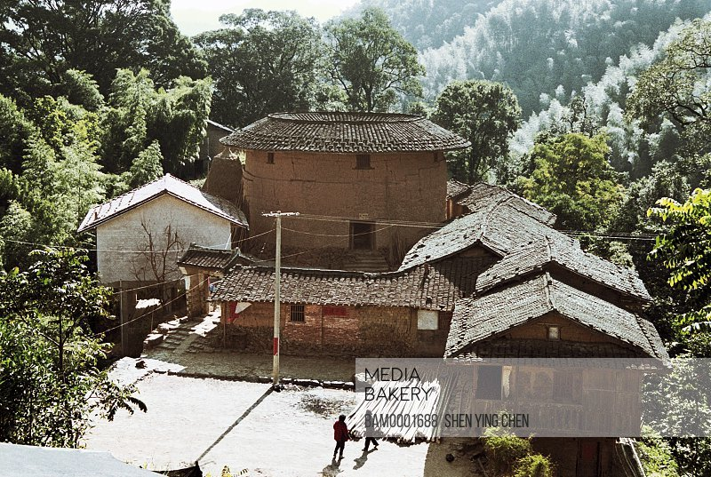 Elevated view of huts with trees in background, Ourdoor scene of the smallest earth building, Cuihui building, Nanjing County, Fujian Province of People's Republic of China
