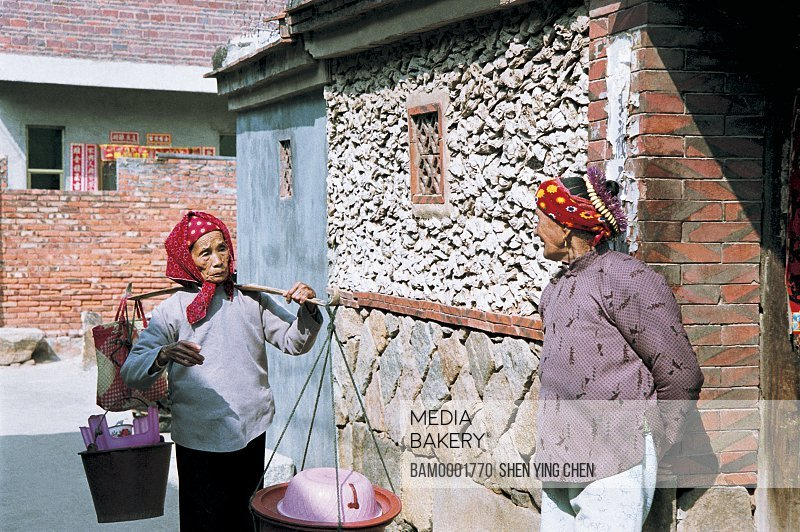 Women standing by door of shell house, Sea oyster shell house of Xunpu Village, Xunpu Village, Quanzhou City, Fujian Province of People's Republic of China