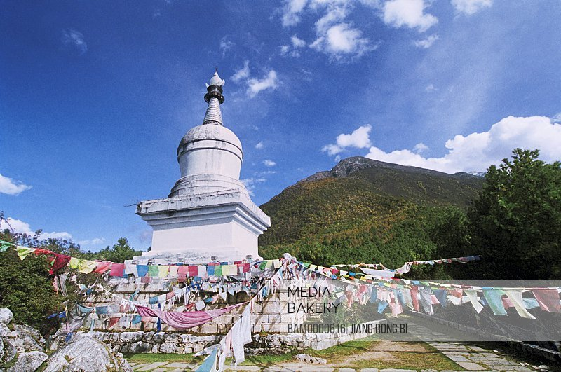 Streamers tied to Buddhist white tower with Panoma mountain in background, The Paoma Mountain buddhist white tower in Kangding, Kangding County, Ganzi State, Sichuan Province of People's Republic of China
