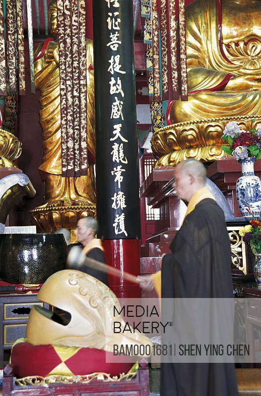 Monks standing in temple holding gong, The buddhist priest chants scripture in Linyang temple, Linyang Temple, Lingtou Township, Fuzhou City, Fujian Province of People's Republic of China