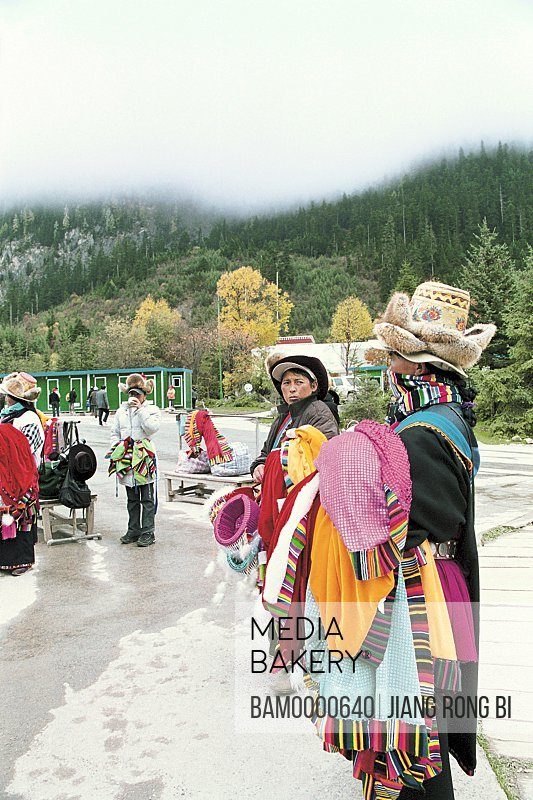Vendors in traditional clothing selling clothes on road, The Zang nationality people in Jiuzhaigou scenic area , Nanping County, Aba State, Sichuan Province of People's Republic of China