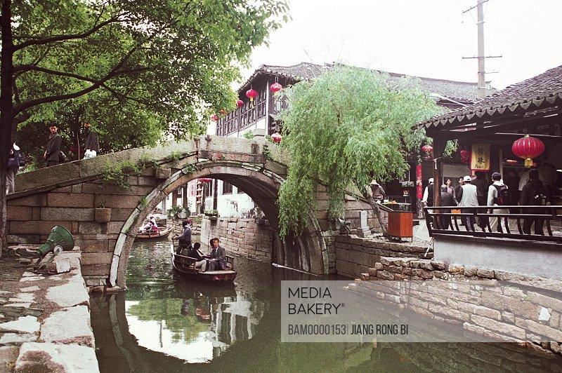 Tourists traveling on a boat, The scenery of bridge of Jiaozhi region of rivers and lakes pond, Jiaozhi Town, Kunshan City, Jiangsu Province of People's Republic of China