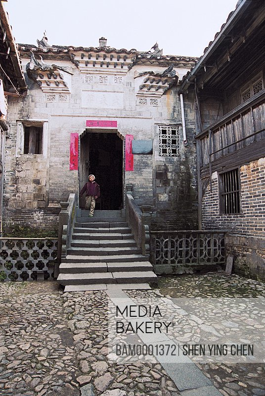 A boy standing on staircase of a house, Ancient common people residence of Ming and Qing Dynasty at old Heping town in Shaowu, Heping town, Shaowu County, Fujian Province of People's Republic of China