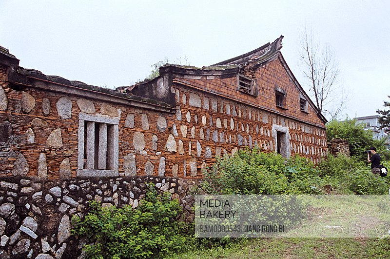 View of a man standing by a house, Houses with Stone-laid Wall in Juren Village, Wangchuan Town, Huian County, Fujian Province, People's Republic of China