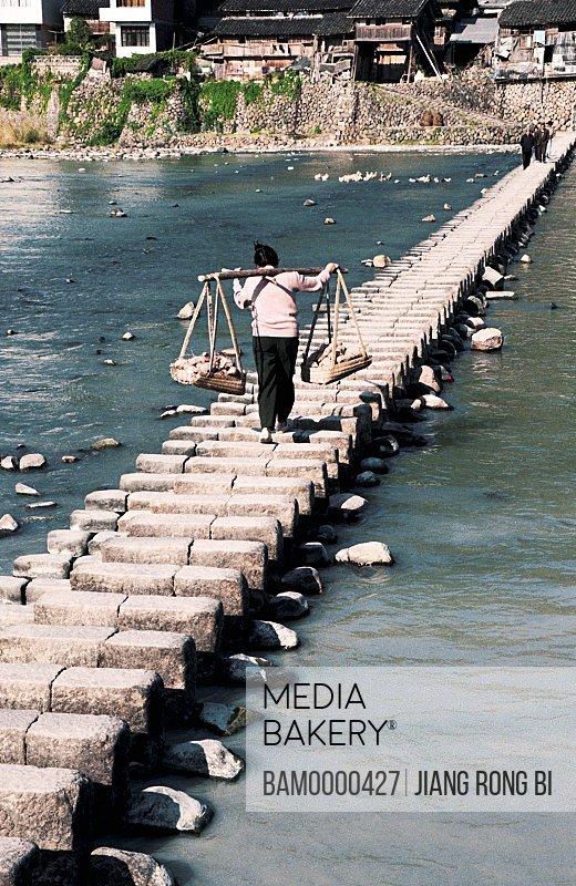 View of a woman walking on foot bridge above river, Shiyangding Footbridge Built in Qing Dynasty, Taishun County, Zhejiang Province, People's Republic of China