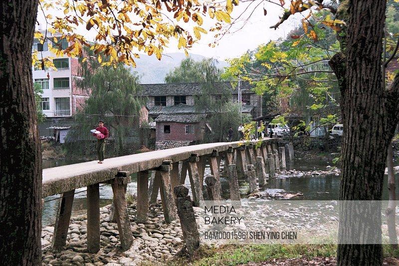 People walking on a stone bridge across the stream, Wanan Bridge of Shouning County, Shouning County, Fujian Province of People's Republic of China