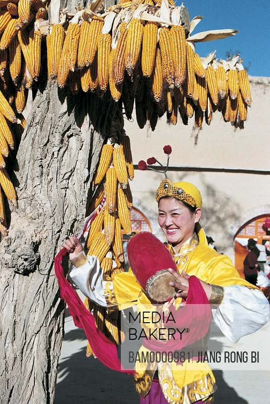 View of a cheerful woman with drum standing by tree, Girls Showing Ansai Waistdrum, Yichuan County, Yan'an City, Shanxi Province, People's Republic of China