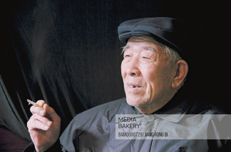 View of senior man holding cigarette, Elder of Retirement, Fuzhou City, Fujian Province, People's Republic of China