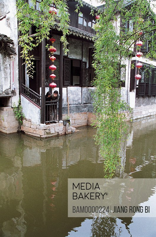 View of people standing in porch of building by canal, Ancient common people residence of Xitang region of rivers and lakes pond, Xitang Town, Jiashan County, Jiaxing City, Zhejiang Province of People's Republic of China
