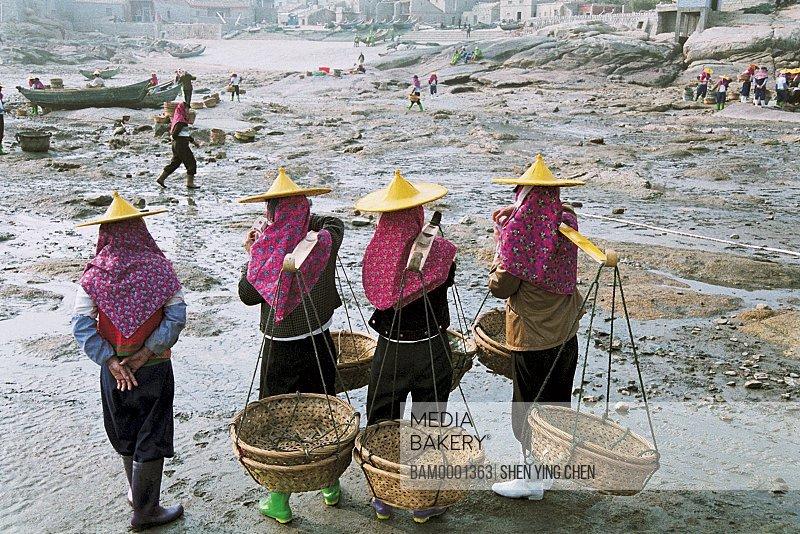 Women carrying baskets at Xiaozuo village wharf, Huian Woman at Xiaozuo Village wharf, Xiaozuo Village, Huian County, Fujian Province of People's Republic of China