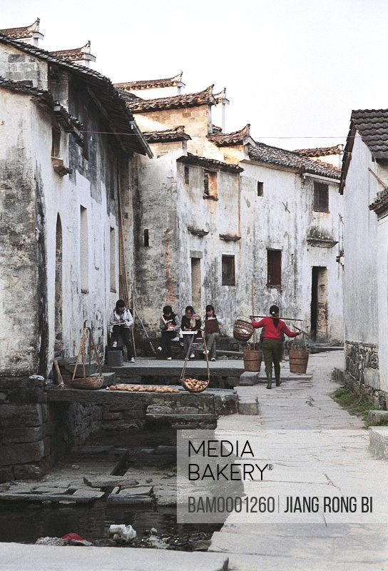 Woman carrying baskets by in a village, Flagstone Road in Ancient Pingshan Village, Yixian County, Anhui Province, PRC