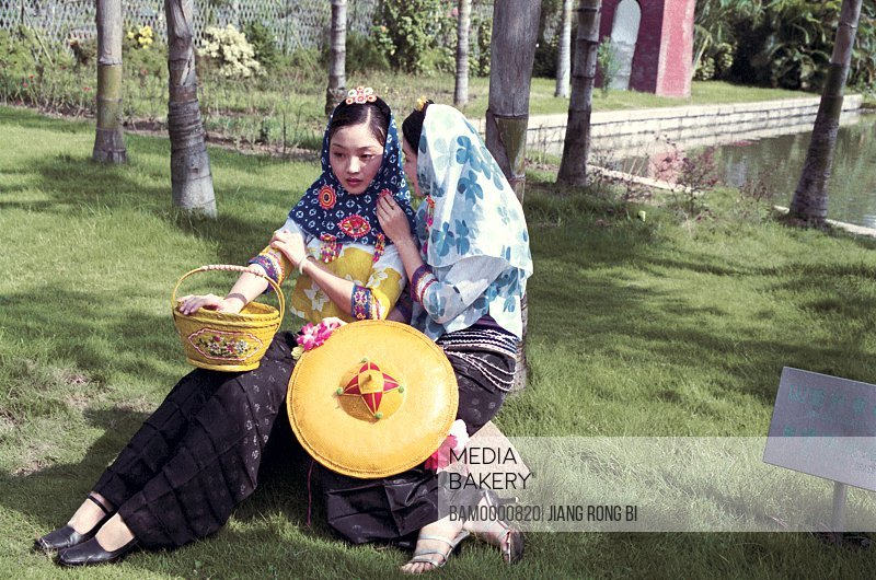 """Young women sitting in park wearing traditional clothing, Huian Ladies Attending Cross-straits """"Photography Festival"""", Fuzhou City, Fujian Province, People's Republic of China"""