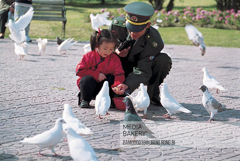 View of man and girl feeding food to pigeons, Wenquan park, Fuzhou City, Fujian Province, People's Republic of China