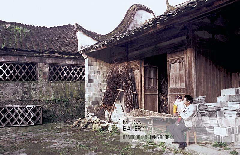 View of man with his daughter sitting by storeroom, Villagers Living in Ancient House, Taishun County, Zhejiang Province, People's Republic of China