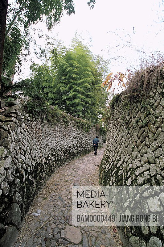 Man walking on passage, Stone-laid Lane in Ancient Furong Village, Nanxi River, Yongjia County, Zhejiang Province, People's Republic of China