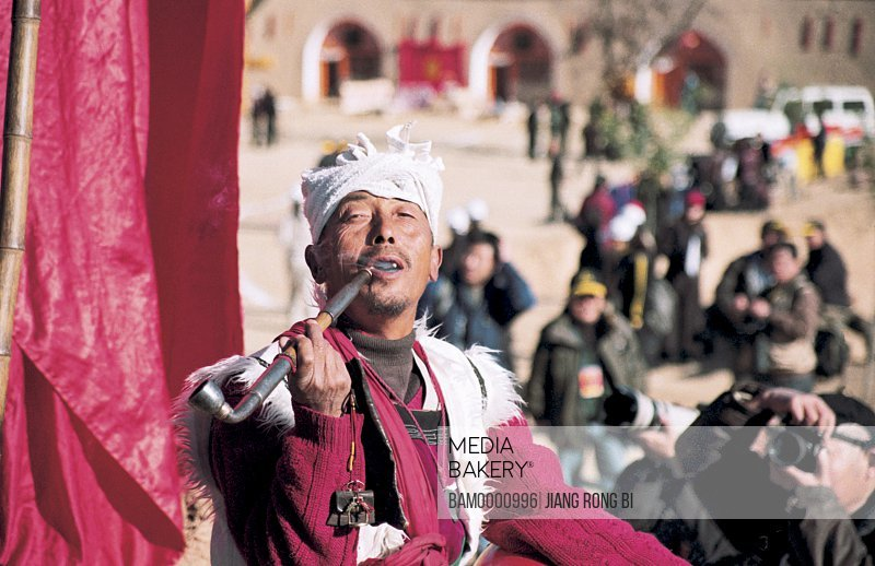 Portrait of a mature man smoking with tourists standing in the background, Old Man of North Shanxi, Yichuan County, Yan'an City, Shanxi Province, People's Republic of China