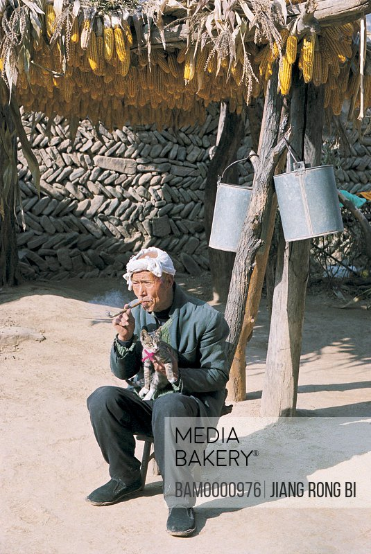 View of a senior man smoking with cat, Pipe-smoking Old Man from Chenjiazhuang Village, Yichuan County, Yan'an City, Shanxi Province, People's Republic of China